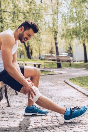 Foto de Young sportsman suffering from pain while sitting on bench and touching elastic bandage on injured knee - Imagen libre de derechos