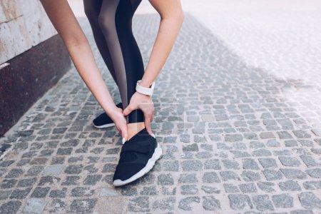Photo pour Vue partielle d'une sportive debout sur la chaussée et touchant une jambe blessée - image libre de droit