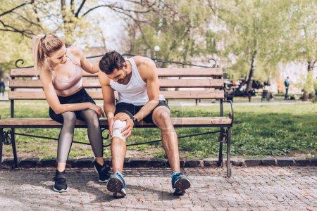 Foto de Deportista lesionado que sufre de dolor en la rodilla lesionada mientras está sentado en el banco cerca de la joven deportista - Imagen libre de derechos