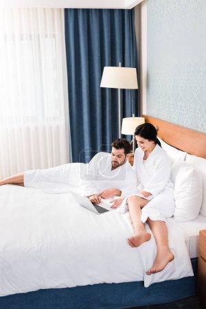 Photo pour Bel homme barbu utilisant l'ordinateur portatif près de la femme gaie dans la chambre d'hôtel - image libre de droit