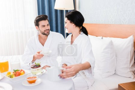 selective focus of happy man and woman near table with breakfast