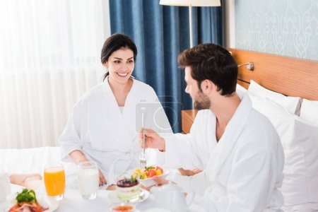 selective focus of happy woman looking at bearded man holding fork near fruit salad