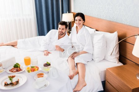 happy man and woman with barefoot looking at breakfast in hotel room
