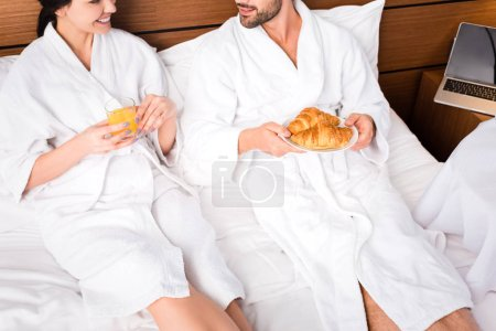 cropped view of cheerful man holding croissants while lying near woman with glass of orange juice