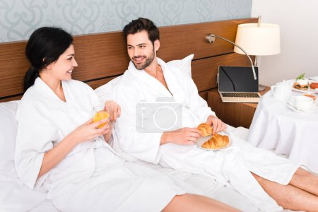 cheerful man holding croissants while looking at woman with glass of orange juice