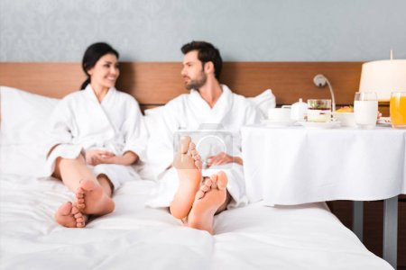 selective focus of happy man and woman looking at each other near table with breakfast