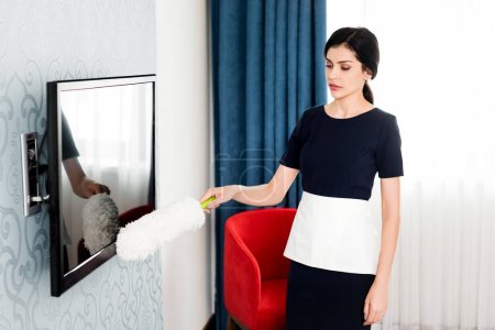 Photo for Attractive maid holding duster while cleaning tv with blank screen in hotel - Royalty Free Image