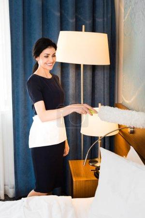 Photo pour Joyeuse femme de ménage tenant le chiffon et nettoyant la chambre d'hôtel - image libre de droit