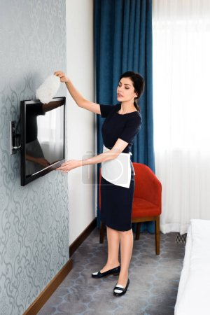 Photo for Brunette maid holding duster while cleaning tv with blank screen in hotel - Royalty Free Image