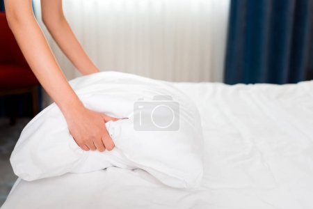 Photo for Cropped view of housemaid holding white pillow in hotel room - Royalty Free Image
