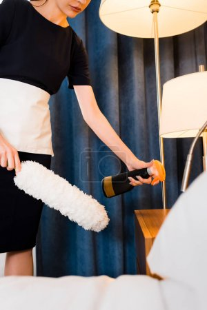 Photo for Cropped view of upset maid holding duster while cleaning hotel room - Royalty Free Image