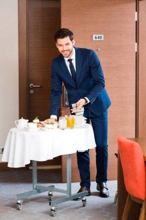 happy receptionist in formal wear gesturing near breakfast in hotel room