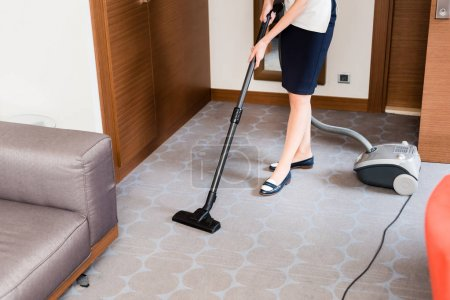 Photo for Cropped view of housemaid cleaning carpet with vacuum cleaner - Royalty Free Image