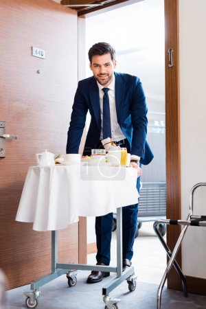 Photo for Selective focus of cheerful receptionist bringing breakfast on hotel food trolley - Royalty Free Image