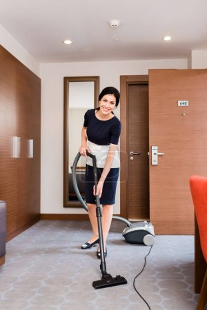 Photo for Happy housemaid cleaning carpet with vacuum cleaner in hotel room - Royalty Free Image
