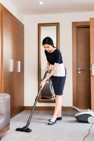 Photo for Brunette housemaid cleaning carpet with vacuum cleaner in hotel room - Royalty Free Image