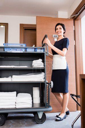 Photo for Low angle view of smiling housemaid in uniform standing near cleaning trolley with white towels - Royalty Free Image