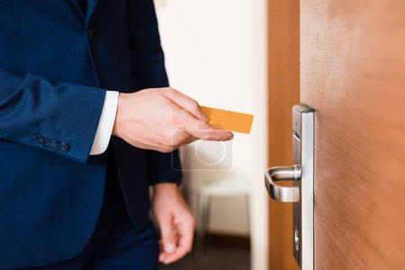 Photo pour Vue recadrée de l'homme d'affaires retenant la carte d'hôtel tout en restant près de la porte - image libre de droit