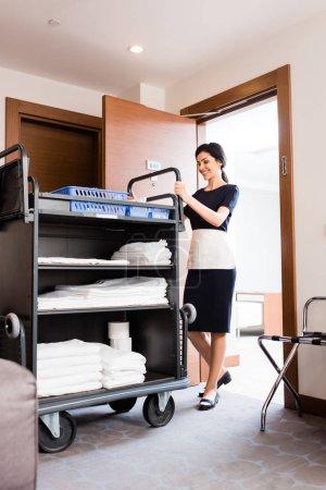 Photo pour Vue bas d'angle de femme de ménage heureuse dans l'uniforme restant près du chariot de nettoyage avec des serviettes blanches - image libre de droit