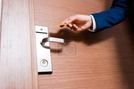 Photo pour Vue recadrée de l'homme retenant la carte d'hôtel tout en restant près de la porte - image libre de droit