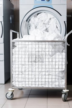 Foto de Carro metálico con ropa de cama sucia cerca de la lavadora en la lavandería - Imagen libre de derechos