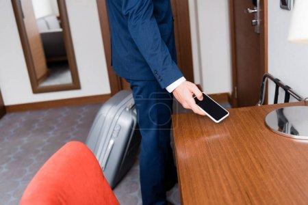 Photo pour Vue recadrée de l'homme d'affaires tenant smartphone avec écran blanc - image libre de droit