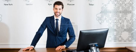 Photo for Panoramic shot of happy receptionist standing at reception desk in hotel - Royalty Free Image