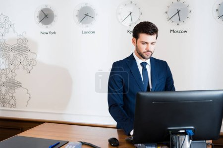 Photo for Handsome receptionist in suit looking at computer monitor in hotel - Royalty Free Image