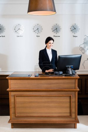 Photo for Cheerful brunette receptionist in formal wear looking at computer monitor in hotel - Royalty Free Image