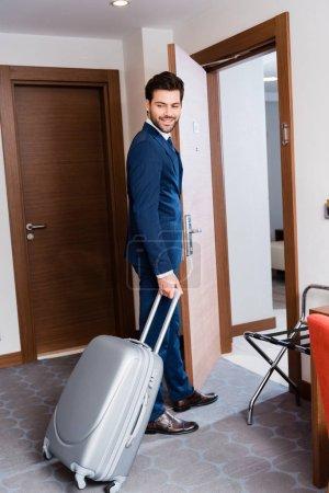 Photo pour Homme d'affaires joyeux en costume souriant tout en se tenant debout avec valise dans la chambre d'hôtel - image libre de droit