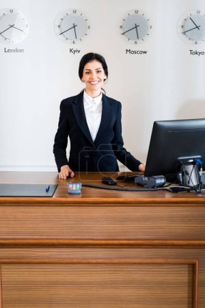 Photo for Cheerful brunette receptionist in formal wear standing near computer monitor in hotel - Royalty Free Image