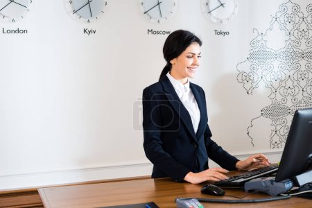 Photo for Happy brunette receptionist in formal wear standing near computer monitor in hotel - Royalty Free Image