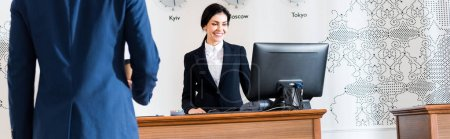 Photo for Panoramic shot of of businessman near cheerful receptionist looking at computer monitor - Royalty Free Image