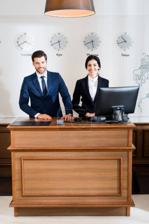 Photo for Cheerful receptionists in formal wear standing at reception desk - Royalty Free Image
