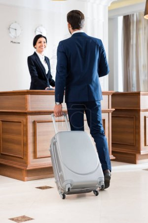 Photo for Selective focus of businessman with suitcase standing near beautiful receptionist - Royalty Free Image