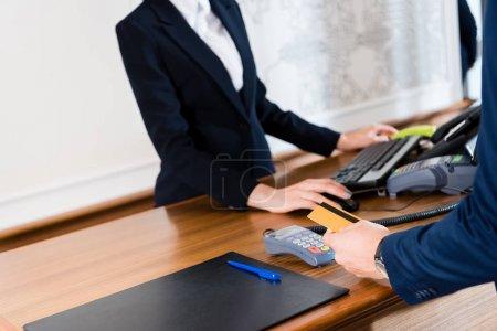 Photo pour Vue recadrée de l'homme payant tout en retenant la carte de crédit dans l'hôtel - image libre de droit
