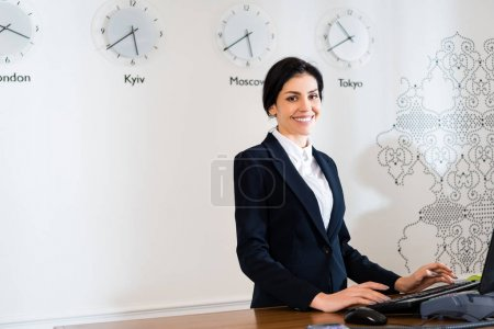 Photo pour Réceptionniste attrayant souriant tout en restant à la réception - image libre de droit