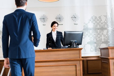 Photo for Back view of businessman near cheerful receptionist looking at computer monitor - Royalty Free Image