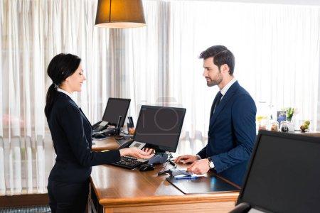 Photo pour Réceptionniste heureux faisant des gestes près de l'homme beau avec la carte de crédit - image libre de droit