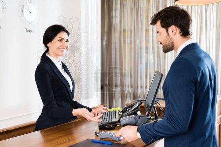 Photo pour Foyer sélectif de heureux geste réceptionniste près bel homme avec carte de crédit - image libre de droit