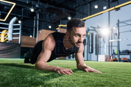 Photo for Handsome bearded man doing plank exercise on green grass - Royalty Free Image