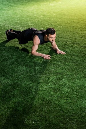 handsome athletic man doing plank exercise on green grass