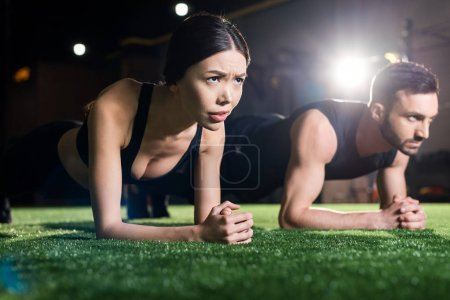Photo for Selective focus of woman doing plank exercise near handsome man on grass - Royalty Free Image