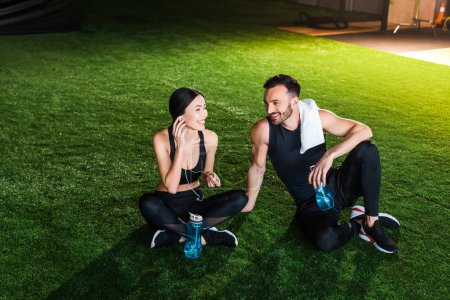 happy woman holding earphones and sitting on grass with handsome man