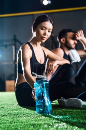 selective focus of woman holding sport bottle near man while sitting on grass