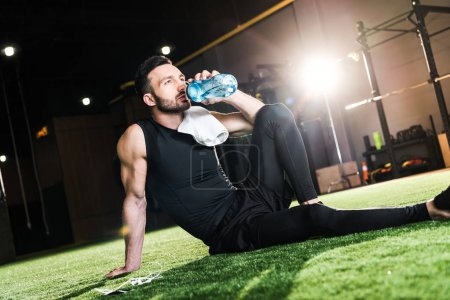 Photo for Handsome man sitting on green grass and drinking water - Royalty Free Image