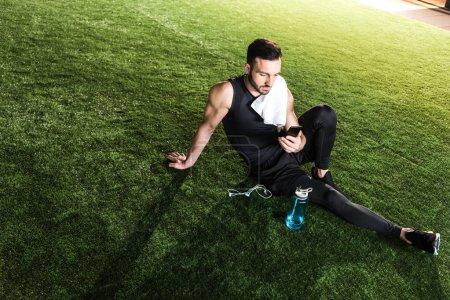 Photo pour Bel homme athlétique utilisant smartphone tout en étant assis sur l'herbe - image libre de droit