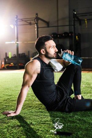 Foto de Hombre atlético guapo beber agua mientras está sentado en la hierba cerca de teléfonos inteligentes y auriculares - Imagen libre de derechos
