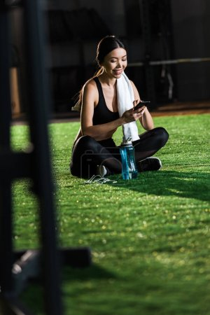 selective focus of happy woman sitting on grass and using smartphone near earphones and sport bottle