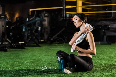 athletic woman holding towel while sitting with crossed legs on grass